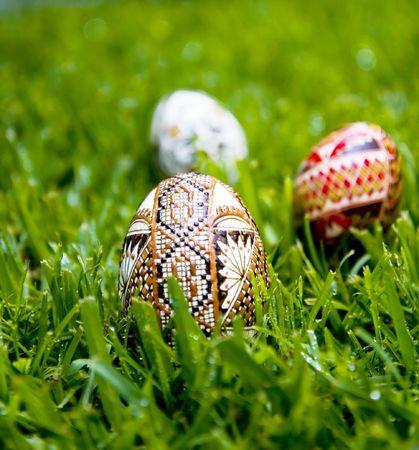 dewey: Tradizionale, a base di uova di anatra decorate a cera fotografato su un letto di erba fresca Dewey. Due uova in pi� sullo sfondo. Profondit� di campo