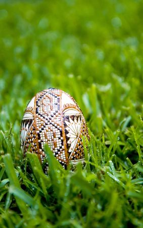 dewey: Traditional hand painted egg (painted with wax) on bright green dewey grass. Shallow depth of field, ample copy space