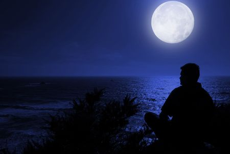 Silhouette of man sitting and thinking by the ocean with full moon shining in the sky.