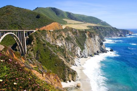 Portion of the Big Sur area on the California coast with turquoise waters crashing on the shore and road bridge