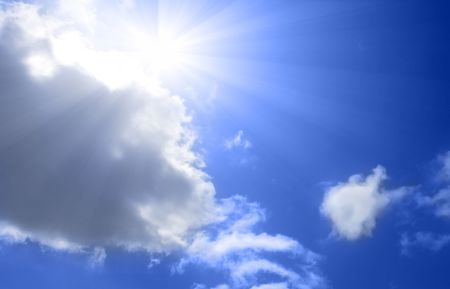 Sun reappearing from behind clouds on brilliant blue sky 免版税图像