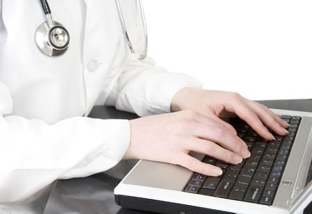 Female doctor or nurse typing on laptop keyboard