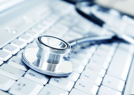 Silver stethoscope on modern silver keyboard photo