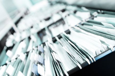 arquivos: Multiple rows of filing cabinets in an office or medical establishment, overflowing with files.  Narrow depth of field to emphasize the neverending feeling