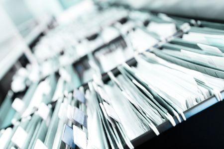 """Plusieurs lignes de classeurs dans un bureau ou établissement médical, débordant de fichiers. Limiter la profondeur de champ pour souligner la """"neverending"""" sentiment Banque d'images"""