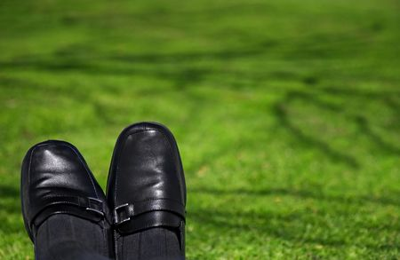 Feet of businessperson looking relaxed on a beautiful shaded lawn. Useful for freedom, vacation,