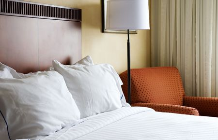 impersonal: Comfortable bed with fresh white linens in hotel room Stock Photo