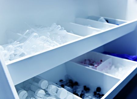 White lab bin full with research supplies in a chemistry or biology lab - cool blue tint
