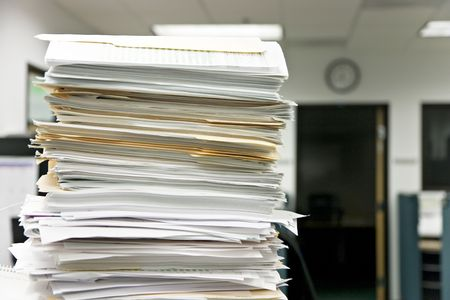 Close-up of a high pile of files, overwhelming the office in the background