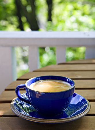 Fresh cup of coffee on a rustic table, for a feeling of a weekend morning in the countryside