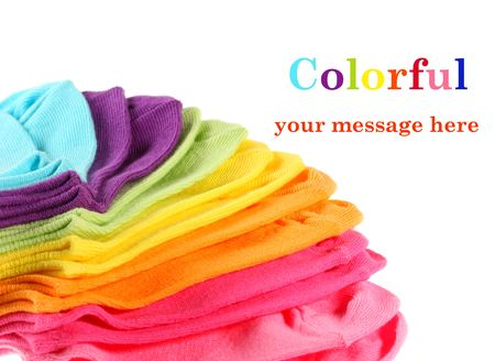 Colorful stack of new kid's cotton socks on white, with copy space .  Focus mid-stack.