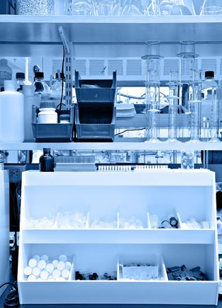 stocked: Typical chemistry lab bench, with many supplies and reagents on the shelves - blue monochrome Stock Photo