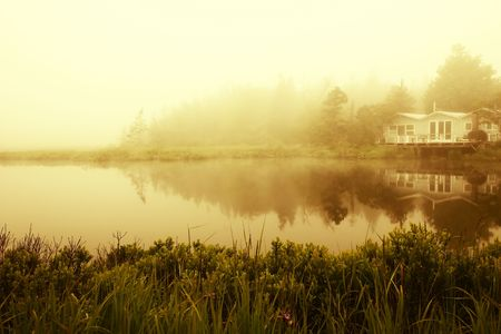 House and grasses reflecting in a misty pond Stock Photo