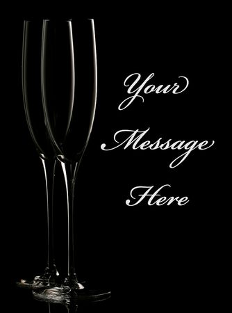 Silhouettes of two champagne flutes against a black background. Simple and elegant, with easily removable sample text photo