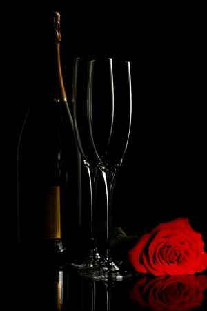 Bottle of champagne with two flutes and a rose, reflected on the table Stock Photo