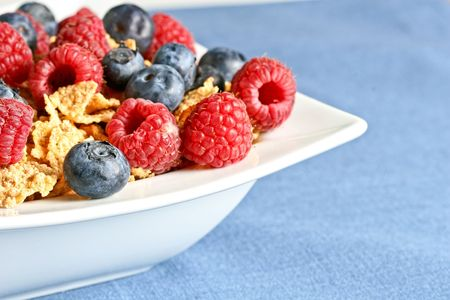 Bowl of berry cereal on blue tablecloth. Shallow depth of field.