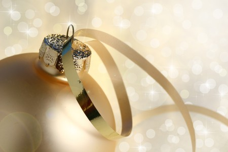 Gold christmas bauble with ribbon on a background of defocused Christmas lights