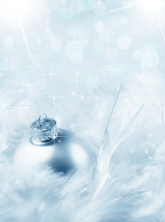 Silver bauble snowy white feather - cold winter blue toning, sparkling bokeh background Stock Photo