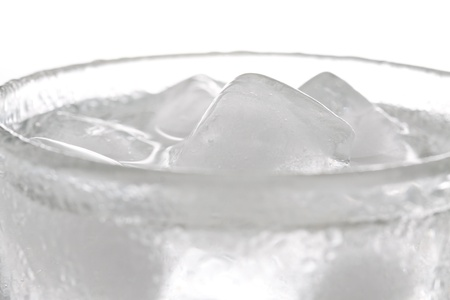 Glass of fresh water with ice cubes, shot with shallow depth of field. photo
