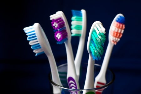 Several toothbrushes inside a glass. photo