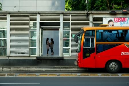 Thamrin Street, Jakarta, 21 september 2009. Twee vrouwen wachten op een trans-Jakarta bus die komt eraan. Deze foto is genomen op Idul Fitri, islamitische feestdag, die het merendeel van moslims terug naar hun geboorteplaats in de landelijke regio van Indonesië, waardoor steden