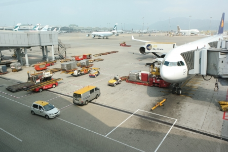 A Lufthansa airplane is being loaded with cargo in preparation for departure at Hongkong International Airport.