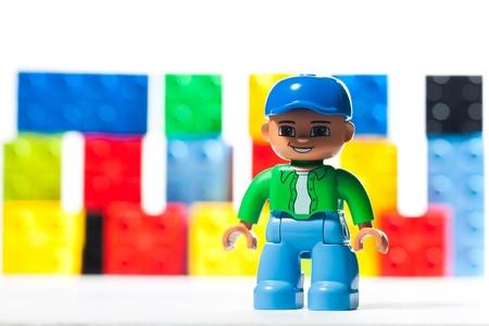 Lego figuur speelgoed met kleurrijke LEGO stenen wazig op de achtergrond.