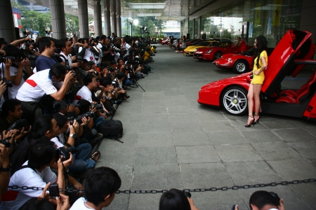 numerous: Jakarta, July 25, 2009. In Ferrari Heritage Photo Competition 2009, Pacific Place, Jakarta, numerous photographers photographing female models with Ferrari sports cars.