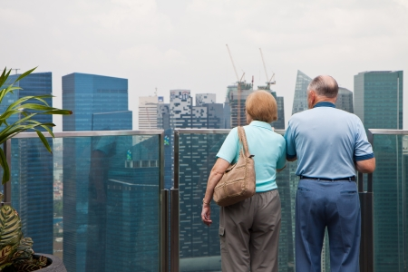 urbanized: Two elderly couple watching Singapore cityscape from the Public Observation Deck of Marina Bay Sands Resorts Hotel.