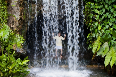 Senior chinese man practising taichi behind an artificial waterfall in Singapore Botanic Garden.