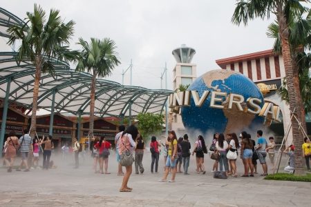 Tourists posing near Universal Studios logo and trademark in Sentosa Resorts World, Singapore.