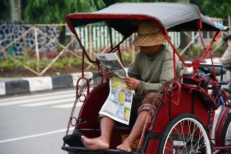 humilde: Un hombre en su peri�dico rickshaw ciclo de lectura en Banjarmasin, Indonesia.