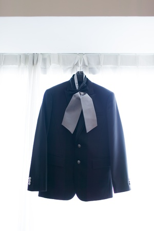 Wedding suit hanging to a window blind. photo