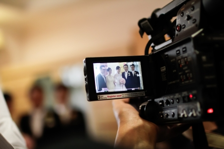 INDONESIA, JAKARTA, 9th March 2012. Video camera recording a wedding ceremony in the brides house.