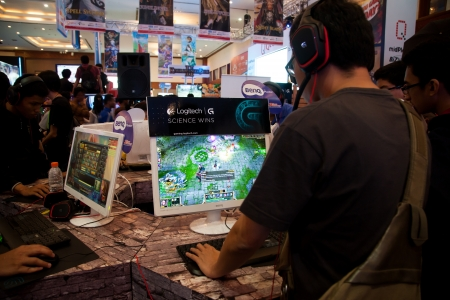 indo: Jakarta, Indonesia, 8th September 2013: Several visitors playing video games on one of the stands at Indo Game Show 2013 event at Jakarta Convention Center, Jakarta, Indonesia.
