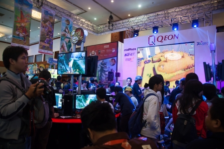 indo: Jakarta, Indonesia, 8th September 2013: Visitors crowding and trying out video games on Qeon stand in Indo Game Show 2013 event at Jakarta Convention Center, Jakarta, Indonesia. Editorial