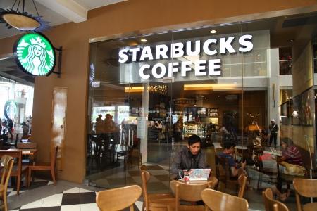Cilandak Stadsplein, Jakarta, Indonesië - 12 oktober 2013: Mensen met een pauze in de Starbucks Coffee op Cilandak Stadsplein, Jakarta. Starbucks Corporation is een internationaal koffie-en koffiehuis-keten gevestigd in Seattle, Washington. Redactioneel