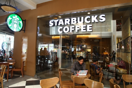 Cilandak Town Square, Jakarta, Indonesia - October 12, 2013: People having a break at the Starbucks Coffee at Cilandak Town Square, Jakarta. Starbucks Corporation is an international coffee and coffeehouse chain based in Seattle, Washington.