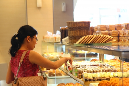 retail chain: Cilandak Town Square, Jakarta, Indonesia - October 12, 2013: A woman picks bread and pastry at BreadTalk Bakery in Cilandak Town Square, Jakarta. BreadTalk is a bakery retail chain based in Singapore.