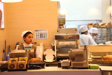 retail chain: Cilandak Town Square, Jakarta, Indonesia - October 12, 2013: A female cashier on her post at BreadTalk Bakery in Cilandak Town Square, Jakarta. BreadTalk is a bakery retail chain based in Singapore.
