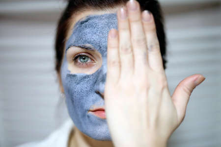 Woman with purifying clay mask on her face. Macro shot with a hand on one half of the face. Stock Photo