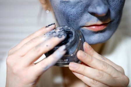 Closeup of woman with mask on her face and glass jar in her hand. Stock Photo