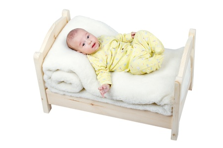 cheerful baby lies in a wooden crib photo