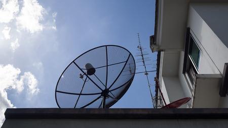 antena parabolica: Antena parab�lica grande, peque�a antena parab�lica rojo y antena de TV en el tejado de la casa contra con el cielo azul y nubes blancas Foto de archivo