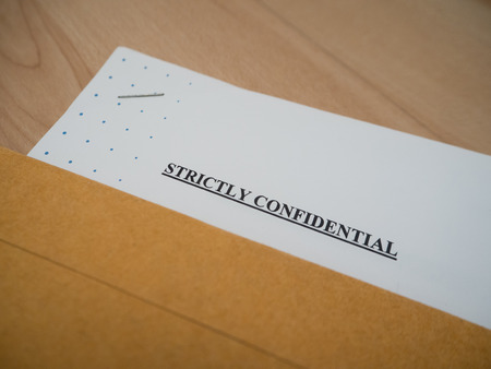 strictly: Strictly Confidential document in brown vintage envelope on wood table, in macro Stock Photo