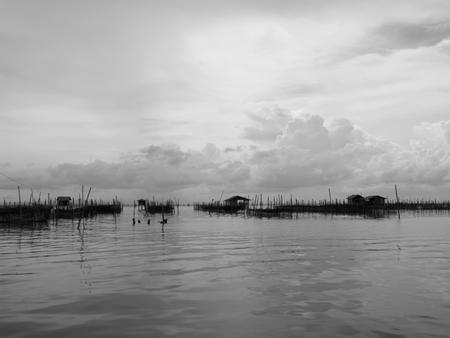fischerei: Schwarz-Wei�-Ton der Gastfamilie und schwimmenden Korb in See bei Kohyo, Songkhla, Thailand mit sch�nen Himmel und Wolken. Das ist traditionelle Fischwirtschaftsgebiet.