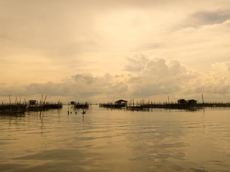fischerei: Vintage-Ton der Gastfamilie und schwimmenden Korb in See bei Kohyo, Songkhla, Thailand mit schönen Himmel und Wolken. Dies ist die traditionelle Fischereigebiet.