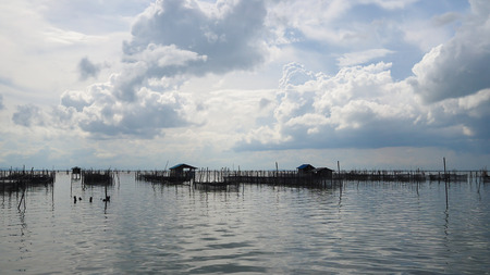 fisheries: Homestay and floating basket in lake at Kohyo, Songkhla, Thailand with beautiful sky and clouds. This is traditional fisheries area. Stock Photo