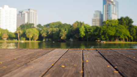 nature natural: Defocus and blur image of terrace wood and water, trees and building inside. Park view in the city, natural background
