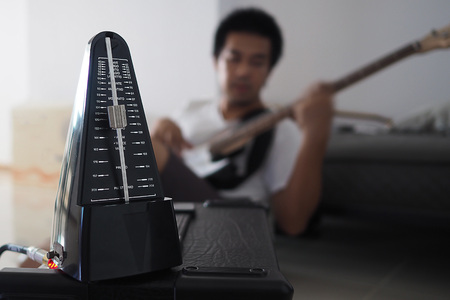 tempo: Black metronome is used by musician to help keep a steady tempo as he play, or to work on issues of irregular timing, or to help internalize a clear sense of timing and tempo. Stock Photo
